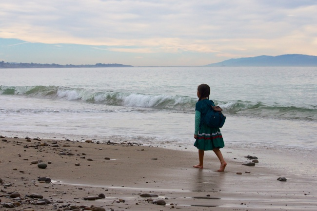 Young girl walking quietly on beach